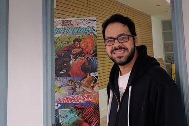 Dimitrios Fragiskatos stands beside a banner for his own comic book series,