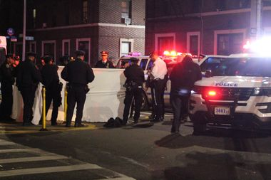 Police hold a sheet up around a woman's body after a fatal crash on Wednesday night.