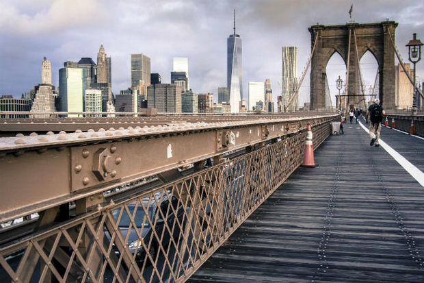 Two Australian tourists were arrested for climbing a beam over the roadway on the Brooklyn Bridge to take photos, police said.
