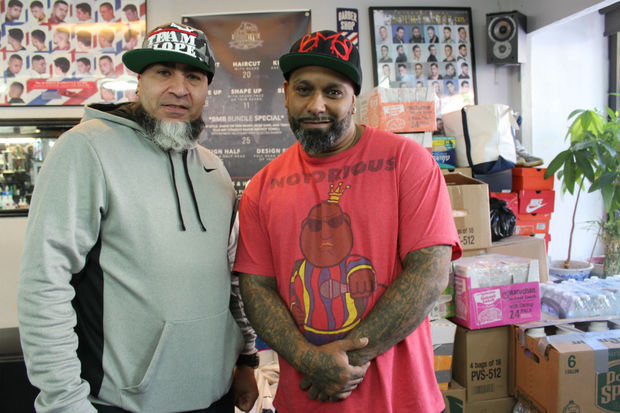 Owner of Brooklyn Master Barbershop Nester Guzman (right) and fellow barber Eric Casanova have converted the barbershop into a hurricane relief drop-off center for Puerto Rico.