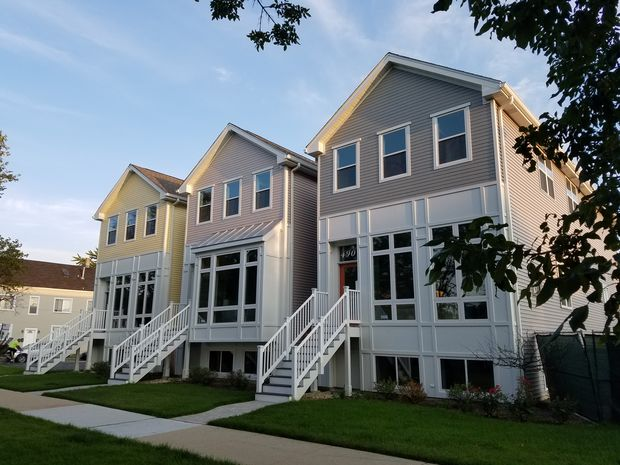The crop of nine newly-built 4-bedroom and 5-bedroom homes line the 4900 block of West Dakin Street.