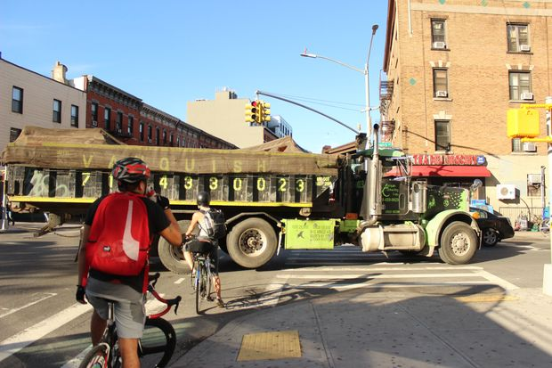 Cyclists wait for a light to change at Bushwick Avenue and Grand Street, where a truck passes on a banned route.