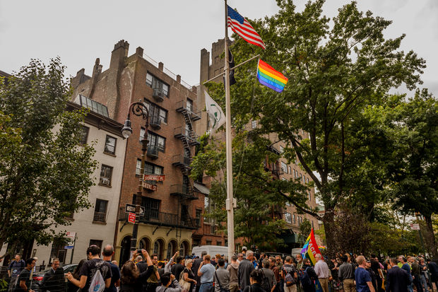 Activists unveil a rainbow flag at Stonewall National Monument on Oct. 11.