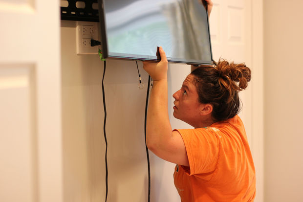 A Fixer handywoman mounts a TV for one of her clients. Fixer is a startup that allows people to request handy services online and pay a flat hourly rate.