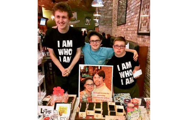 Nate Simon (middle) stands beside fellow salespeople for I Am Who I Am's bath products. This line of soaps, lotions, bath bombs and more will be for sale at HollyDays from 6-10 p.m. Saturday at both Barney Callaghan's Pub and Cork & Kerry in Beverly.