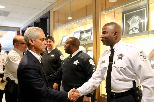 Mayor Rahm Emanuel greets a police officer Monday at an event designed to showcase the deployment of additional officers.