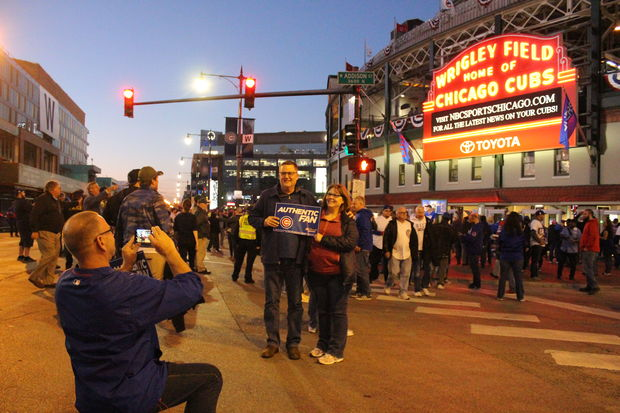 Fans pose for photos outside Wrigley Field's iconic marquee before Game 3 of the NLCS on Tuesday.