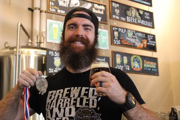 Matt Johnsen holds a silver medal he took home from the Great American Beer Festival Oct. 7. The brewer helped create Biere de Voleurs, which was awarded second place in a category for French- and Belgian-style ales.
