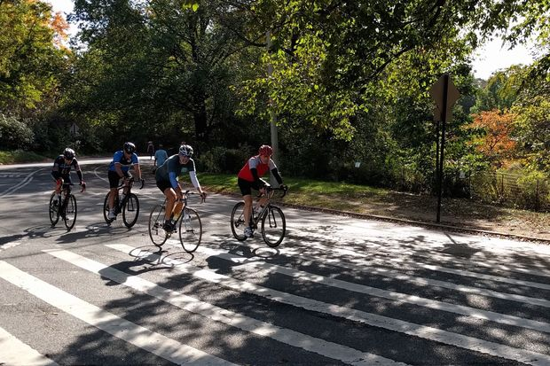 Cyclists bike on Prospect Park's main drive near Grand Army Plaza on Monday.