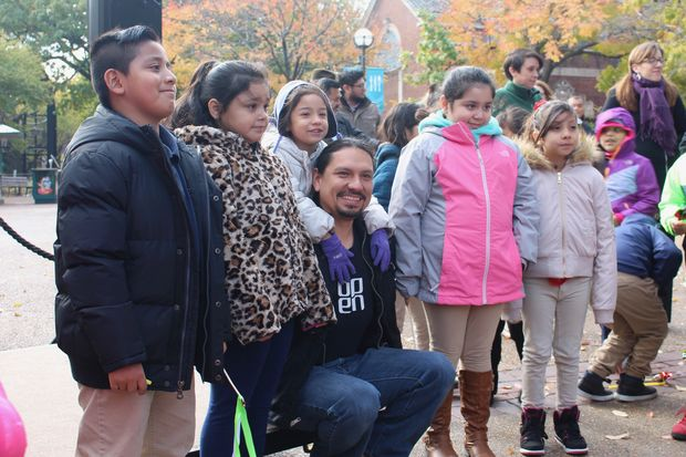 Student artists Jimena Hernandez (left) and Nahi Morales and Jocelyn Argueta (right) join sculptor Omar Magana (embraced by his daughter) at Monday's unveiling of the chimp sculptures at Lincoln Park Zoo.