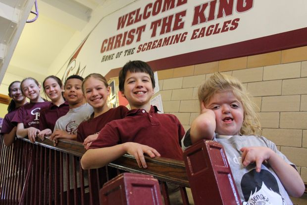 Mary Cate Lynch (front) stands on the stairs at Christ the King School in Beverly with a group of sixth grade students. The students attended a preview of