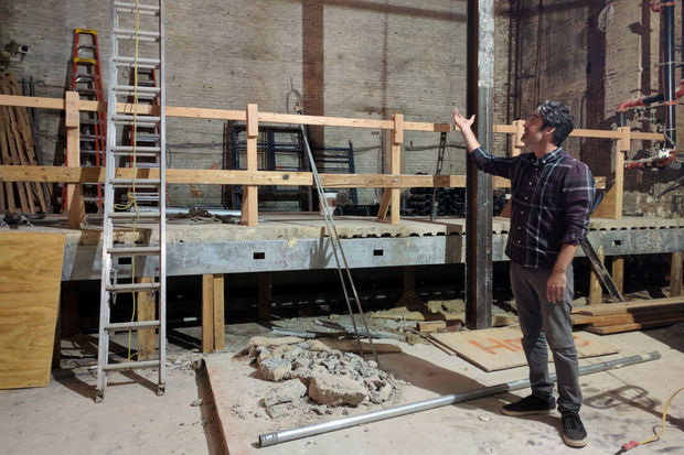 Nitehawk's owner Matthew Viragh gesturing toward what once was a sprawling vaudeville stage with a 50-foot high fly space. The space will be divided into a handful of theaters.
