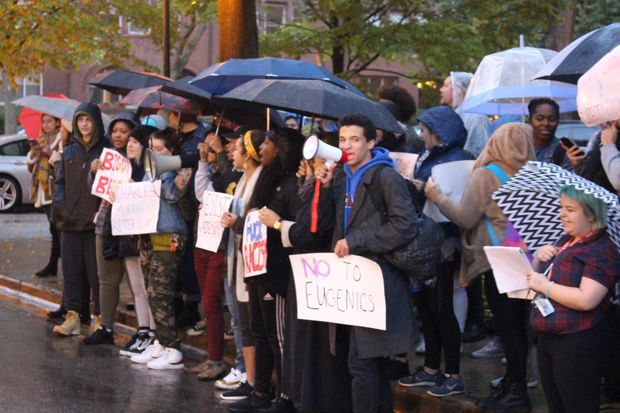 DePaul students protest in the rain outside a campus appearance by conservative author Charles Murray Wednesday.