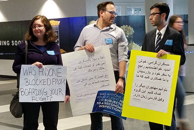 Attorneys hold signs addressed to people flying in to O'Hare's international terminal. They have been volunteering to help immigrants and refugees.