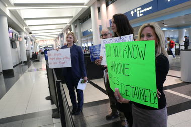 Volunteers hold signs addressed to people flying in to O'Hare's international terminal. Attorneys and others have set up camp in the airport as they try to help immigrants and refugees.
