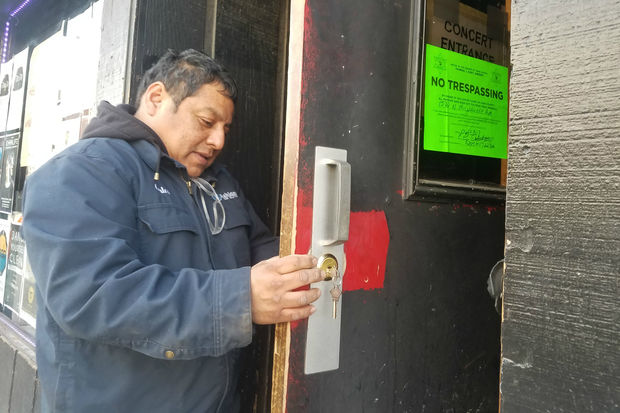 A man changes the locks at the Double Door, 1572 N. Milwaukee Ave.
