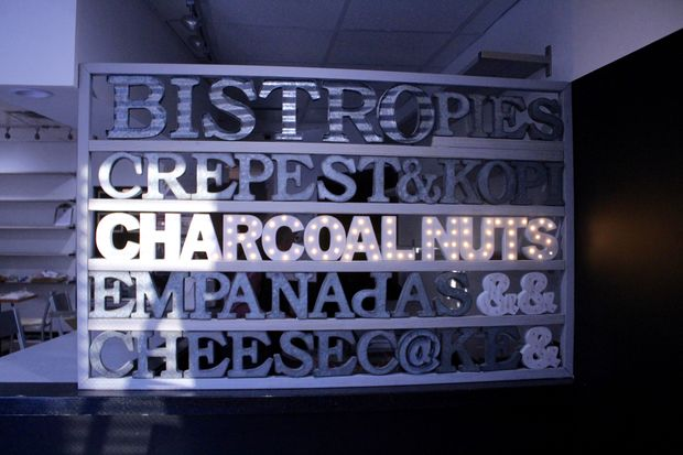 A light-up sign inside Bistro 6050, whose menu includes sweet and savory bites from around the globe.
