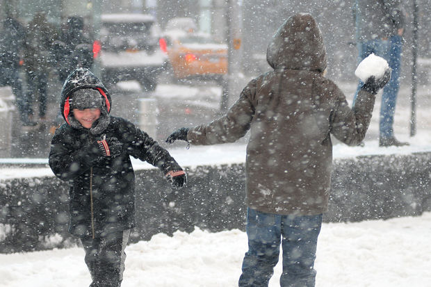 Children play in the snow in Times Square on Thursday, Feb. 9, 2017.