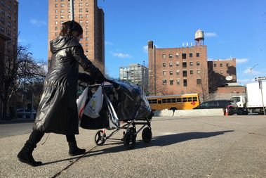 An Orthodox woman pushes a stroller through La Parada, where day laborers usually gather for work. Most took the day off for