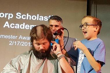 6th-grader Noah Padilla takes an electric clipper to social studies teacher Vince Coughlin's head.