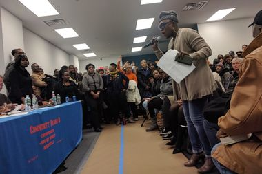 Crown Heights resident Qumarah Jackson, right, questions city officials about security and screening of residents at a shelter to open at 1173 Bergen St. later this month.