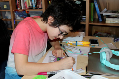 Sasha Harmon Matthews, 12, works on a cartoon superhero likeness of Cara Rosenburg, an avid reader and girl scout.