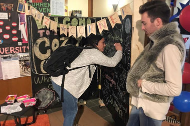 Students write on a chalkboard at the Tough to Be Tough Cozy Corner, loosely modeled on the way Cub fans drew on the Wrigley Field falls after last year's championship.