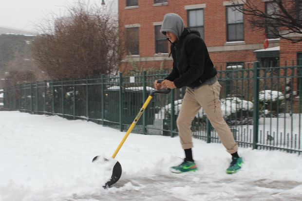 Shannon Pierre, 25, shovels snow on Fulton Street in Fort Greene.