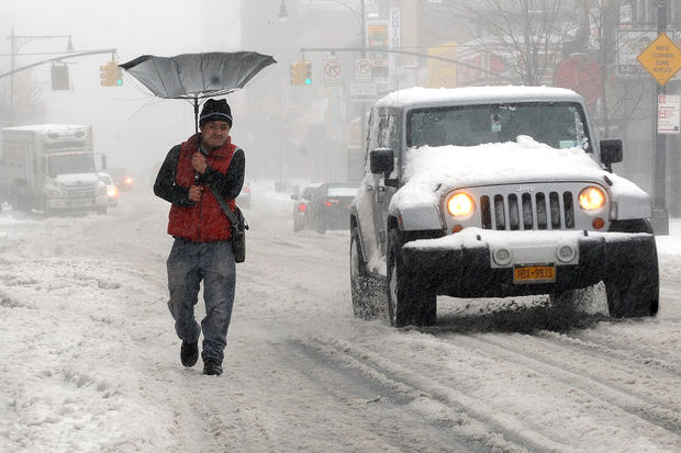 A man braves the snowstorm on Fulton Street and Nostrand Avenue.