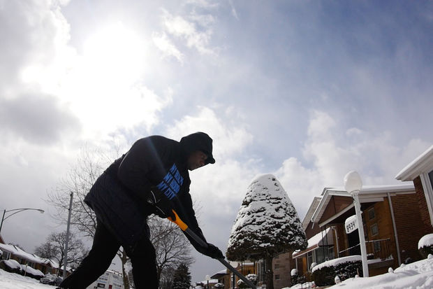 Jahmal Cole helped shovel snow for seniors Tuesday at 89th and Yale.