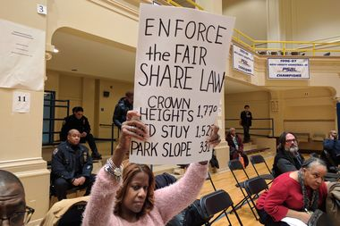 A resident holds up a sign telling the city to enforce the
