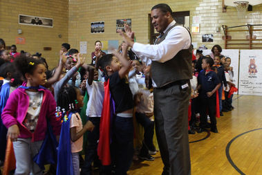 Principal Derrick Orr high-fives caped Manierre students at the start of Monday's award assembly.