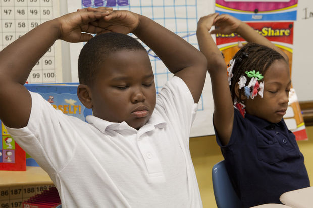 Chicago children do  a classroom mindfulness exercise.