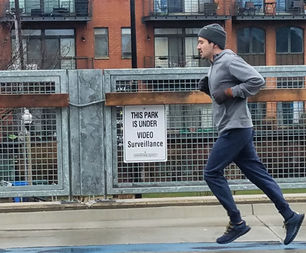 A runner on The 606 in front of a new sign notifying people that the park is under video surveillance.