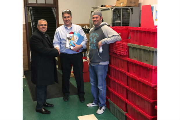 Ald. Gilbert Villegas (36th) with Reinberg principal Ed Loch and CVS district manager Robert Greenlee, standing next to the 24 crates of donated supplies
