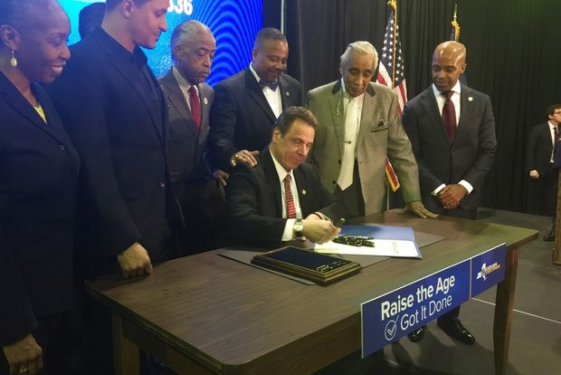 Gov. Cuomo signed the bill into law in Harlem surrounded by advocates, lawmakers and prosecutors.