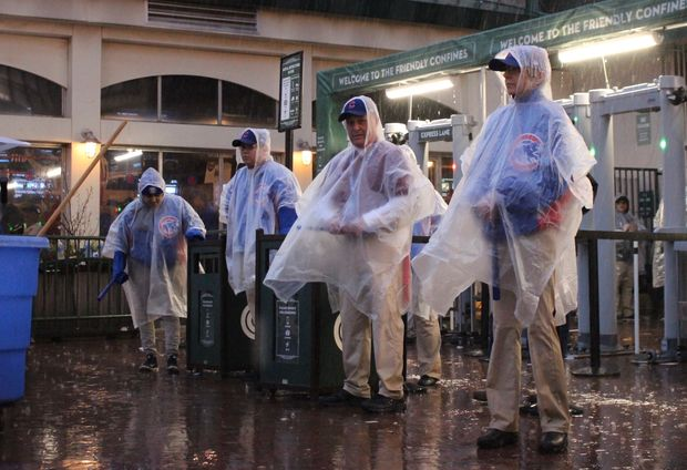 Cubs employees covered themselves with ponchos as a sudden downpour delayed the Cubs home opener. The Cubs are once again facing rain during Tuesday's Game 4 at home.