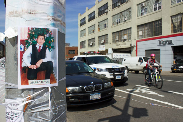 A photo of Gelasio Reyes taped to a post at 43rd Avenue and 39th Street, where he was struck and killed on April 1 while riding his bike. Nearby, an NYPD car blocks the bike lane.