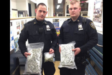 Police officers from the 110th Precinct hold the 2 pounds of marijuana they confiscated from a driver's trunk in Elmhurst on April 13, 2017.
