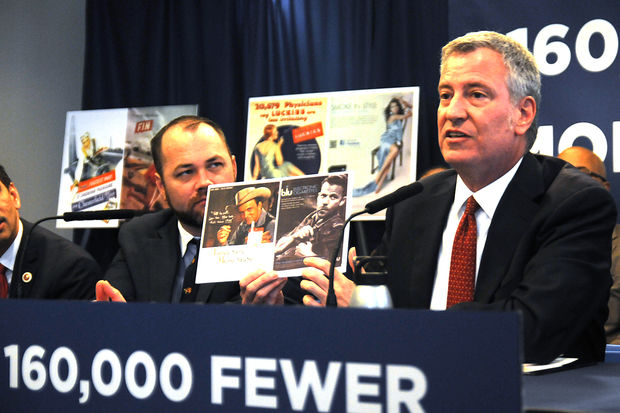 Mayor Bill de Blasio holds up examples of old and new smoking advertisements during a press conference to announce a series of bills to reduce the number of smokers in the city, April 19, 2017.