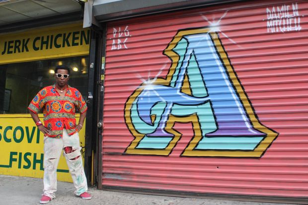 Artist Pierre Francillon stands next to the first mural in the