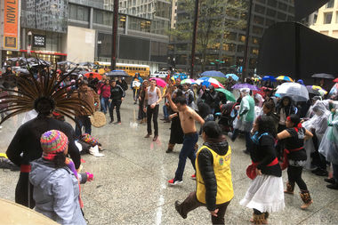 Protesters and students gathered at a rainy Daley Plaza on May Day 2017.