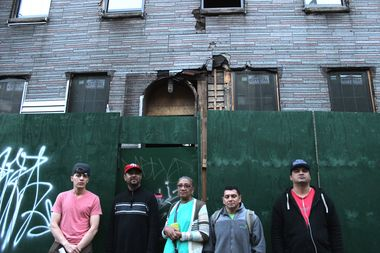 Neris Ramirez, Franklin Montero, Paula Herrera, Jorge Ventura and Jose Cruz stand in front of the building they used to live in.