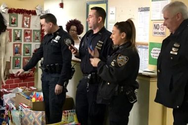Neighborhood Coordination Officers giving out toys to kids at the South Jamaica Houses earlier this year.