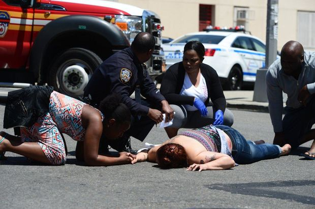 People comfort a woman after she was struck by an NYPD police car in Crown Heights on Tuesday.