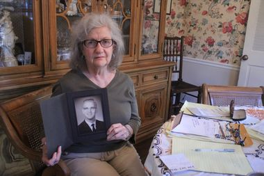 Nancy Jack holds a high school yearbook photo of her brother, Loren