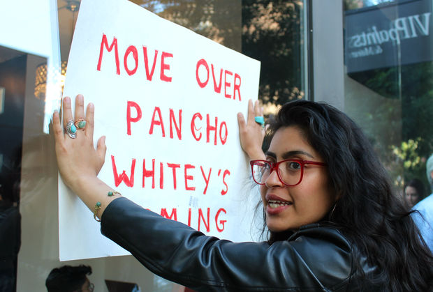 Pilsen resident Xochyl Perez holds a sign that reads