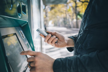 A man can be seen using an ATM in this stock photo.