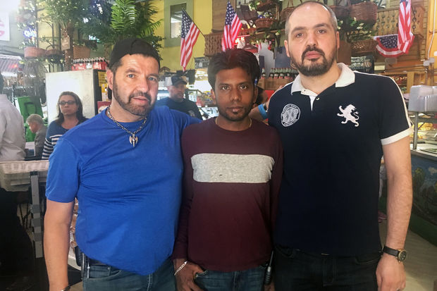 Amish Market workers Michael Jording, Jamal Micah and Umit Tacettin (l-r) stand together after the West Broadway market reopened Thursday following carbon monoxide leak that injured 32 workers.