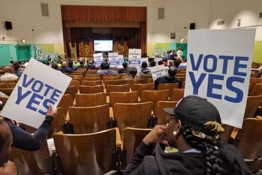 Supporters of the Bedford-Union Armory redevelopment held up signs at a CB9 ULURP hearing on Monday. After hearing testimony from more than 50 people, the committee voted unanimously against the project.
